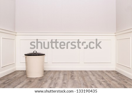 Trash can in the corner of vintage room with wood like rubber floor, laminate floor
