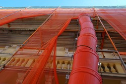 Trash chute or debris chute in red color on a facade of a historic building in reconstruction for rubbish removal. The house is covered with red protective net. The photo is taken at low angle.