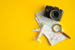 Travel accessories on yellow background. Vintage camera, airplane, magnifying glass and map. Minimalist flat lay style composition, top view. Travel planning concept