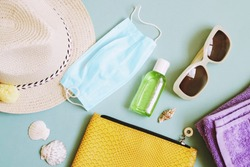 Travel after lifting restrictions during the coronavirus COVID-19 pandemic. Sun hat, cosmetic bag, protective face mask, sanitizer gel and sunglasses