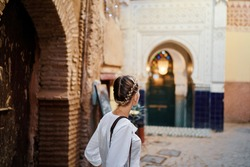 Travel and active lifestyle concept. Young traveller woman walking in ancient moroccan town.