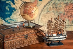 Travel and explore the world concept. Discover the world in old style. Close up on a globe map next to a old ship model, old airplane model, luggage and binoculars. World map in background.