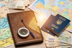 Travel and finance concept. On the table is a compass, geographic maps, Ukrainian money and Ukrainian foreign passports.