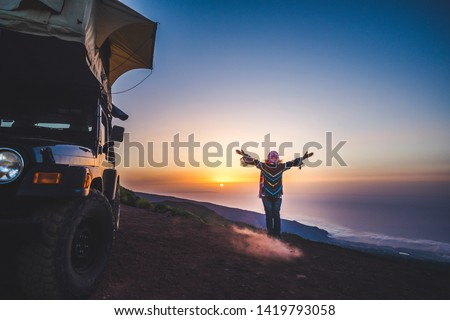 Travel and happiness concept for wanderlust people - woman with coloured warm clothes enjoy freedom and sunset near a car with tent on the roof - independence and wild traveler lifestyle female