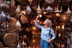 Travel and shopping. Young traveling woman with choose presents in copper souvenir handicraft shop in Morocco.