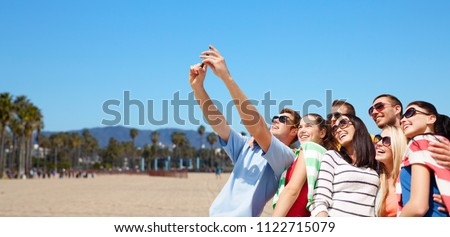 travel and tourism concept - group of happy friends taking selfie by cell phone over venice beach background in california #1122715079