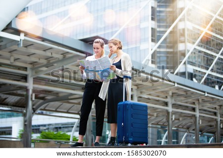 Travel and tourism concept. Two caucasian Woman traveler tourist walking with luggage and looking the map in the city