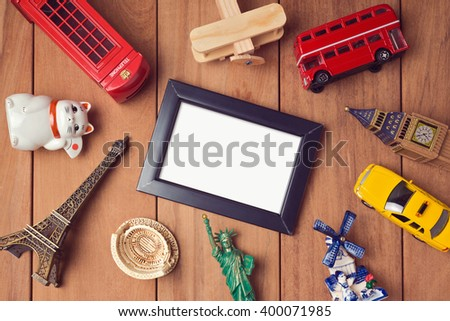 Travel and tourism concept with frame mock up template and souvenirs from around the world. View from above