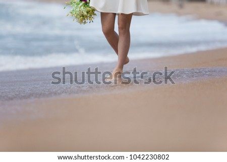 Travel and tourism. The legs of the girl go along the beach. #1042230802