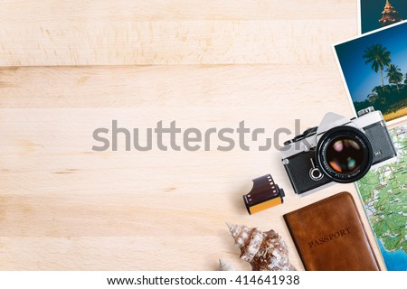 Travel and vacation concept. All photographs are taken by me. Items on aged wooden table. Vintage SLR film camera, old photos, film roll, sea shells, passport and map. Top view with copy space