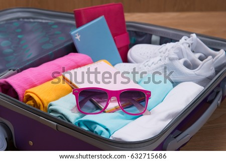 Travel and vacations concept. Open traveler's bag with clothing, accessories, credit card, tickets and passport. #632715686