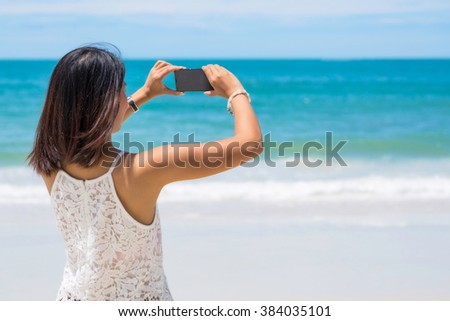 Travel asia woman taking photo on sea beach with mobile smart phone camera