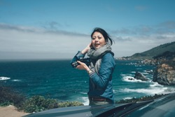 travel asian woman photographer holding professional camera shooting smiles while visiting Big Sur along the California State Route Highway 1 along the pacific ocean. girl resting enjoy view near car