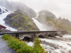 Travel attraction. Powerful twin waterfall Latefoss or Latefossen and six arched bridge along Route 13, Odda Hordaland County in Norway.