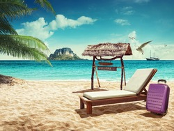 Travel. Beach chair and suitcase on sand beach. Concept for rest