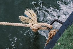 Travel Boat Rope Secured To Cleat On Wooden Dock With Dark Water Below, Tied rope knot on metallic bollard , seafaring port. Nautical ship moored in dock. Anchor rope in the port, ship mooring tool.