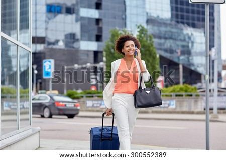 travel, business trip, people and technology concept - happy young african american woman with travel bag walking down city street and calling on smartphone