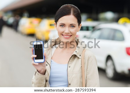 travel, business trip, people and tourism concept - smiling young woman showing smartphone blank screen over taxi station or city street