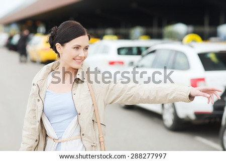 travel, business trip, people, gesture and tourism concept - smiling young woman waving hand and catching taxi at airport terminal or railway station