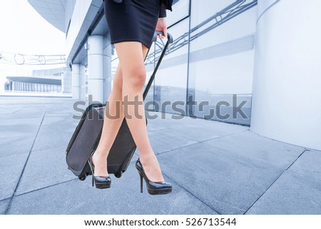 travel business woman pulling suitcase bag walking along sidewalk outdoors in modern urban city #526713544