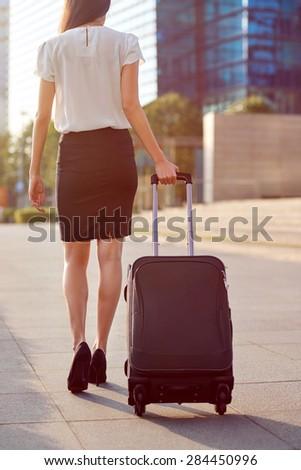 travel business woman pulling suitcase bag walking along sidewalk outdoors in urban city
