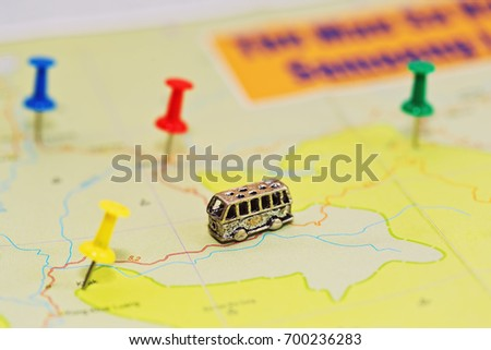 Travel by bus concept with geographical roadmap - close-up capture with different pushpins and tiny bus figurine. Macro capture with small depth of field. No cities or other objects names. #700236283