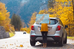 travel by car. Road trip -  tourist girl with a map is standing near the car. Austria. roadtrip