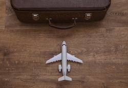 Travel concept. Air plane and old travel suitcase on wooden floor. Top view