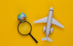 Travel concept. Airplane, magnifier with a globe on yellow background. Top view. Flat lay