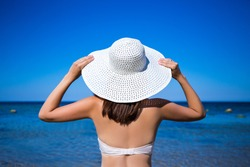 travel concept - back view of slim woman in bikini and hat looking at the sea