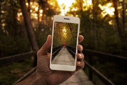 Travel concept, close up of a male hand photographing person in the forest