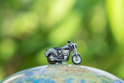 Travel Concept. Close up of miniature motorcycle toy on wolrd balloon map with green nature background.