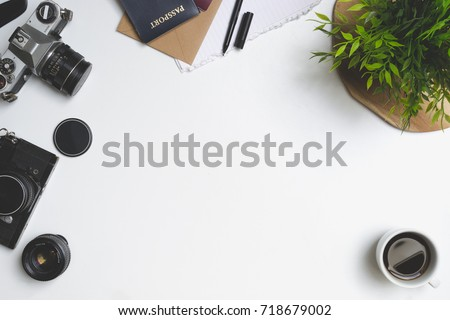 Travel concept. Desk or table filled with (office) supplies. Old vintage camera, envelope, notebook, pen, plant, coffee, passport, phone and lens. View from above.
