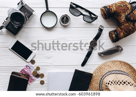 Travel concept,  documents, hat, compass, money, phone and camera on a white wooden background #603961898
