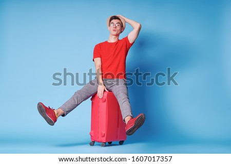 Travel concept. Full length colorful studio portrait of young man in hat with valise on blue background.