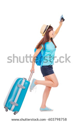 Travel concept. Full length studio portrait of pretty young woman holding passport with tickets running with luggage. Isolated on white.