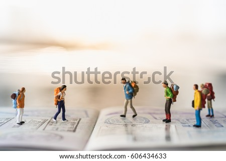 Shutterstock Travel Concept. Group of miniature people figures with backpack walking and standing on passport with immigration stamps.