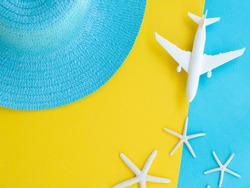 Travel concept on yellow and blue pop background. Straw hat, plain toy, and starfishes. Minimal flat lay