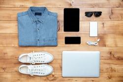 Travel concept shoes, shirt, mobile phone, laptop,mp3, usb, eyeglasses, tablet on the desk