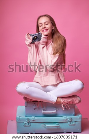 Travel concept. Studio portrait of pretty young woman holding camera sitting on baggage valises. Pink background.