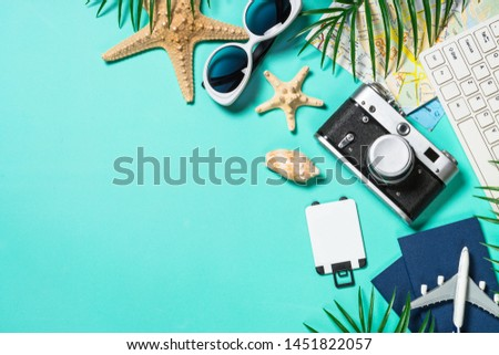 Travel concept. Summer holiday trip background. Old film camera, hat, sunglasses, starfish and palm leaves on blue background. Top view. Flat lay.