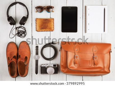 Travel concept - tablet pc, headphones, camera, shoes, watch and bag on the desk