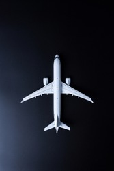 Travel concept. Top view of Jet airliner on black background. Commercial passenger or cargo aircraft, business jet ready for flight