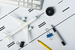 Travel concept. Top view of Jet airliner on office desk like aircraft on runway. Online flight purchase, flight tickets booking