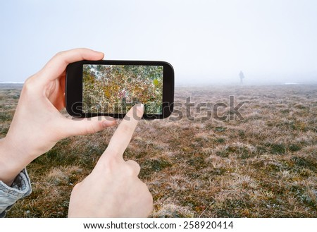 travel concept - tourist taking photo of Arctic tundra in spring, Siberia, Chukotka on mobile gadget Russia
