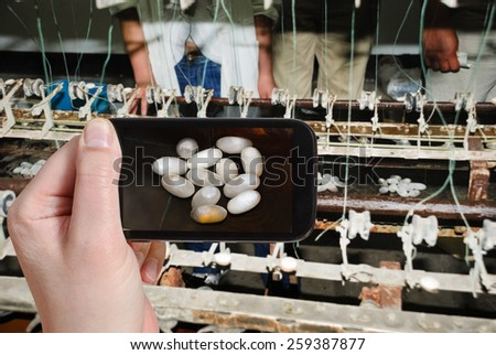 travel concept - tourist taking photo of extracting raw silk fibre from cocoons on mobile gadget, China