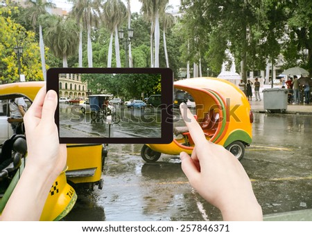 travel concept - tourist taking photo of Havana street in rain on mobile gadget, Cuba