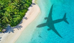 Travel concept with airplane shadow and tropical beach. Tropical paradise and beach holiday conceptual image.