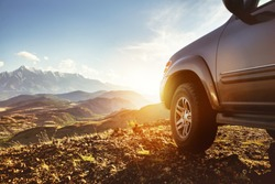 Travel concept with big 4x4 car against sunset and mountains. Closeup photo of offroad wheel