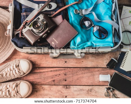 travel concept with travel bag, retro camera and travel accessories on wooden background.